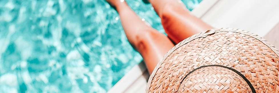 Frau mit Hut am Pool